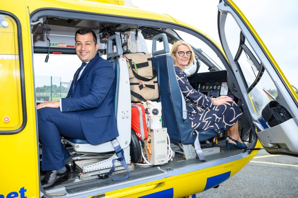 image of two people sat in a helicopter smiling